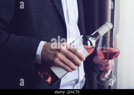 Cierre horizontal de caucásico hombre en traje negro y camisa blanca verter vino rosado en un vaso de una botella en un bar por la ventana natural li