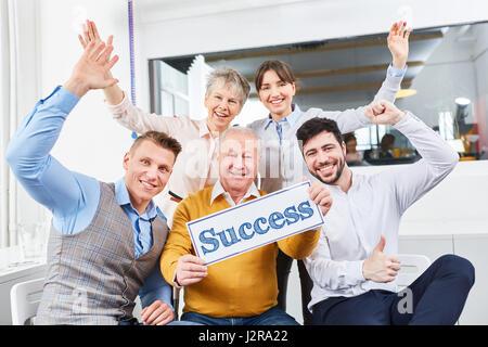 Equipo empresarial tiene letrero que indica éxito como ganador y el concepto de trabajo en equipo