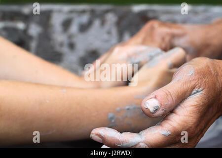 La alfarería, la enseñanza de la alfarería. Mujer de edad avanzada, las manos de una pequeña degustación las manos del niño alrededor de arcilla como hacer cerámica juntos.