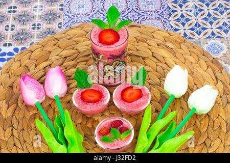 Una taza de jugo de fresas con hojas de menta sobre un fondo de colores orientales / taza de jugo de fresas sobre un fondo de colores orientales con flor
