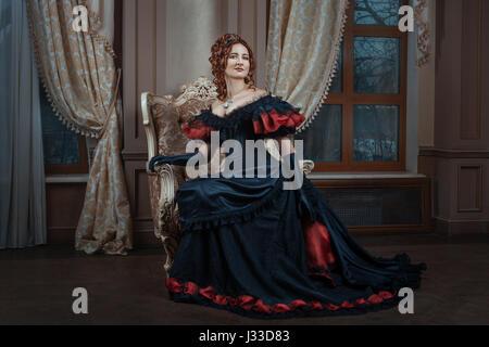 Mujer de vestido Victoriano sentada en una silla en la habitación. Foto de stock
