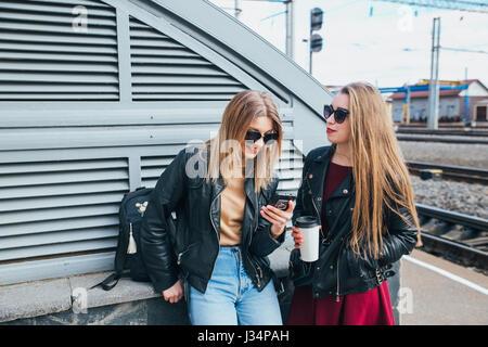 Dos mujeres hablando en la ciudad.Outdoor Lifestyle retrato de dos mejores amigos hipster niñas vestían elegante chaqueta de cuero y gafas de sol con cafetería, enloqueciendo y teniendo mucho tiempo juntos
