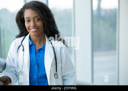 Closeup retrato de agradable, sonriente, seguro de salud femenina con bata de laboratorio profesional, el estetoscopio, brazos cruzados. Hospital clínico aislado atrás
