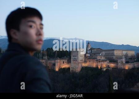 Turismo Asiático en frente del Palacio de la Alhambra en la fotografía, desde el Mirador de San Nicolás en el barrio Albayzin en Granada, Andalucía, España. Los palacios nazaríes con la Torre de Comares, la Iglesia de Santa María de la Alhambra y el Palacio de Carlos V, se ve en la foto de izquierda a derecha.