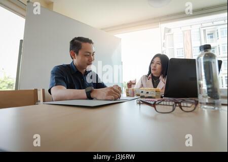 La empresaria asiática y debatir ideas con jóvenes hombre freelance en la sala de reuniones. Inicio ideas de negocios y trabajo en equipo concepto