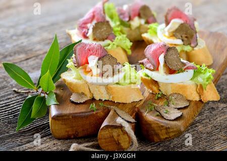 Canapés con roast beef, otoño negras trufas, queso brie francés sobre una rebanada de huevo en baguette con una hoja de ensalada