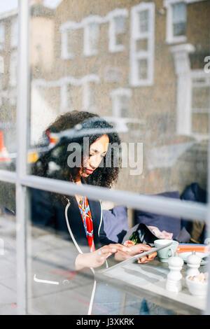 La vista de la ventana de la mujer mediante tableta digital en cafe