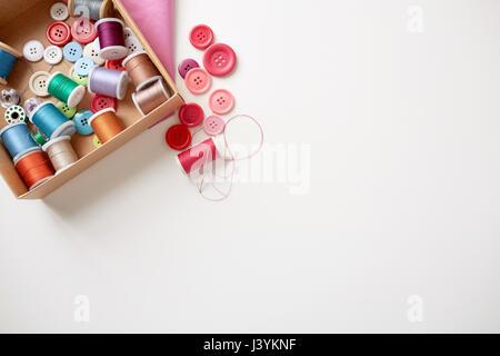 Caja con carretes de hilo de coser y los botones de la tabla