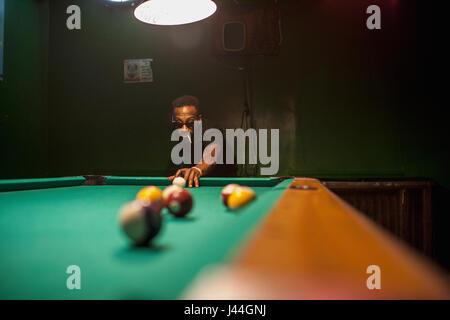 Un hombre joven jugando al billar.