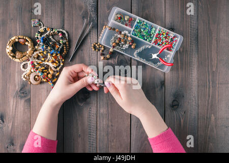 Hacer de la joyería artesanal. Caja con cordones sobre fondo de madera vieja. Accesorios hechos a mano. Vista superior
