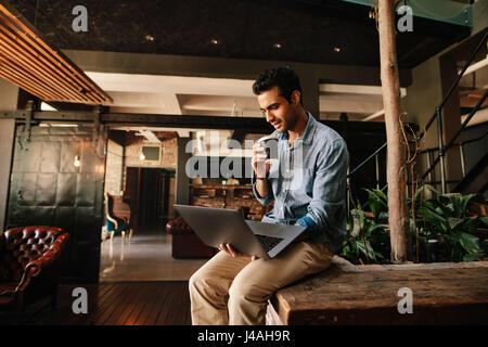 Foto de hombre joven sentado relajado mirando el portátil y con café. Utilización Portátil ejecutivo masculino durante la pausa para el café.
