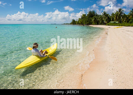 Mujer kayak en las aguas turquesas de Tikehau, Tuamotus, Polinesia Francesa, el Pacífico