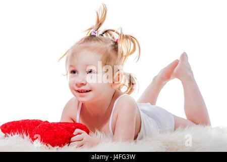 Gracioso feliz niña niño acostado en la cama sosteniendo almohada aislado Foto de stock
