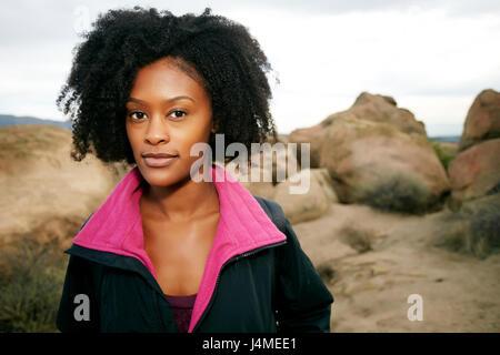 Retrato de mujer negra seria posando sobre formación de roca Foto de stock
