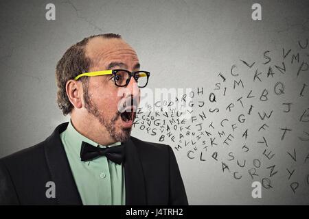 Vista lateral vertical hombre de negocios de mediana edad hablando con las letras del alfabeto que sale de la boca abierta aislada pared gris de fondo. Rostro humano expressio