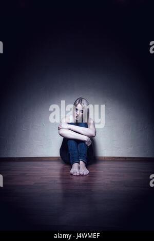 Triste joven mujer sentada sola en el piso de una habitación vacía