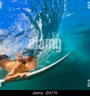 Active chica en bikini en acción. Surfer mujer con surf buceo bajo submarino Rompiendo olas grandes. Estilo de vida saludable. Deporte acuático, surf extremo