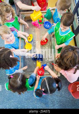 Vista aérea de una clase de la guardería de niños jugando en una mesa de agua. Se trata de usar todos los delantales y con juguetes de plástico.