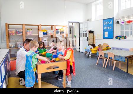 Grupo de niños en un aula de párvulos. La mayoría están jugando en la mesa de agua y tres niños están jugando en la mesa de arena.