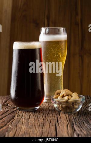 Dos pintas de cerveza artesanal sentado en un bar rústico de madera. Cervecería artesanal ale y porter.