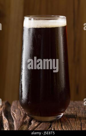 Una pinta de cerveza artesanal sentado en un bar rústico de madera. Microcervecería porter.