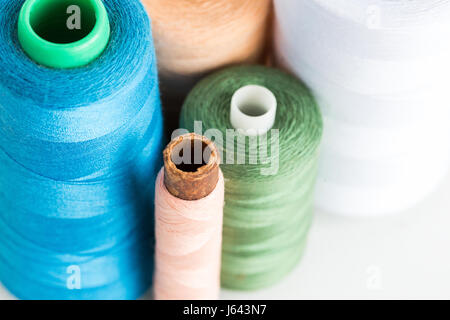 Costura, patchwork y adaptando el concepto - cerca en azul, verde, blanco, albaricoque y hilos de color rosa en bobinas de nuevo sobre fondo blanco en un taller, vista superior.