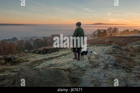 Mujer paseando a un perro en una ruta en Ilkley Moor en una helada mañana temprano buscando en vistas a la campiña de una nube de inversión, Wharfe Valley, Yorkshire, Reino Unido