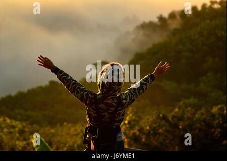 Vista trasera de la mujer de pie con los brazos en el aire