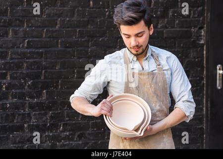 Potter, utensilios, cerámica arte concepto - sonriendo macho en el delantal ceramista presenta muestras de productos de arcilla, artesano la posesión de los nuevos recipientes acabados, feliz maestro sobre fondo gris oscuro de pared de ladrillo.