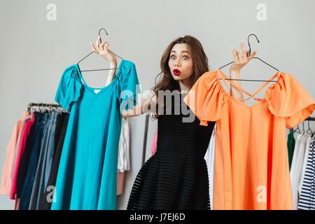 Foto de confundirse joven de pie en la tienda de ropa interior elegir entre dos vestidos. Mirando a un lado.