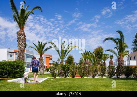 Madre caminando con su pequeña hija en lindo hotel complejo entre palmeras. Vista trasera.