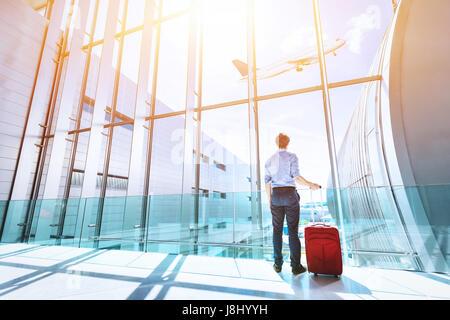 Empresario a la terminal del aeropuerto Boarding gate mirando avión volando a través de la ventana Foto de stock