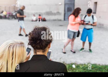 Grupo de amigos jugando juego de realidad aumentada con teléfonos móviles