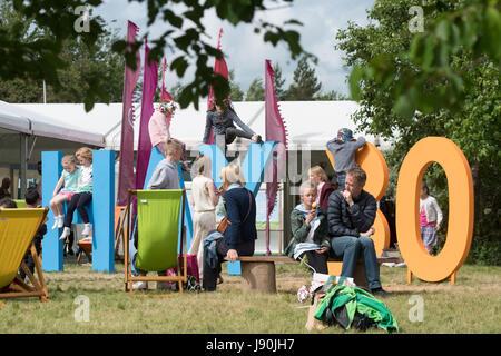 """Hay Festival, Gales, Reino Unido, Martes 30 de mayo de 2017 niños jugando en el sol en el gigante 'heno 30' firmar en la 6ª Jornada del Hay Festival 2017, en la pequeña localidad galesa de Hay On Wye rural en Powys. Ahora en su 30º año, la literatura festival atrae a algunos de los mejores escritores, académicos y analistas de todo el mundo, y decenas de miles de visitantes cada día a lo que fue descrito por el ex presidente estadounidense Bill Clinton como """"el Woodstock de la mente"""" Crédito Foto © Keith Morris / Alamy Live News"""