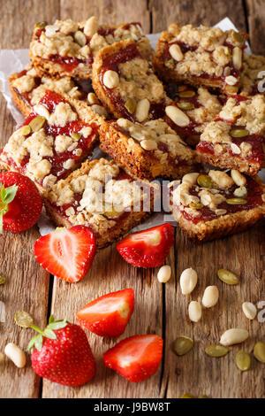 Barras de granola con mermelada de fresa, semillas y nueces de cerca en la tabla vertical.