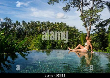 La mujer disfruta de una piscina desbordante por encima de un valle en el Kamandalu Resort Ubud, en Ubud, Bali, Indonesia, Sudeste Asiático, Asia