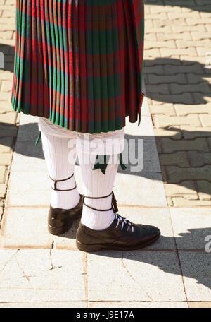 Tartán rojo y verde falda escocesa. Highlander vistiendo ropas tradicionales de Escocia. Gaiteiro uniforme: falda y calcetines de la rodilla