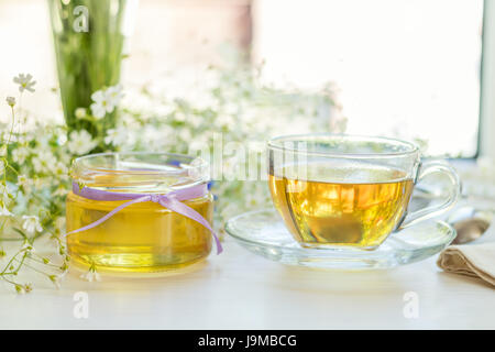 La Miel en tarros de vidrio y una taza de té con flores blancas de primavera sobre el alféizar. Profundidad de campo.