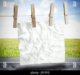 Papel arrugado blanco colgado en una lavandería línea sobre tablas de madera con el cielo azul en el fondo