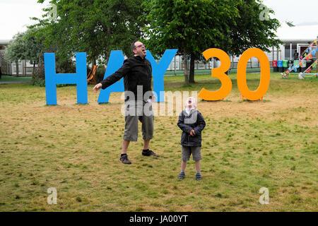 Un padre y su hijo jugando delante del heno 30 aniversario firmar atrapar la lluvia en la boca abierta en el año 2017 FESTIVAL DE HENO HENO-on-Wye Gales UK KATHY DEWITT