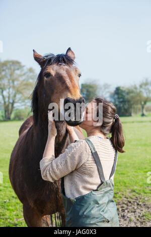 Mujer de pie al aire libre, un beso en la mejilla de caballos marrones. Foto de stock