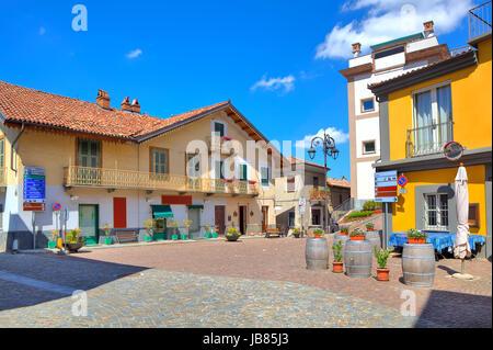 Pequeña plaza adoquinada en el centro de un típico pueblo italiano entre coloridas casas en Barolo, Italia.