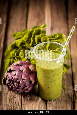 Vegetarianos saludables alcachofa y lechuga batido con ingredientes frescos en una vieja mesa de cocina de madera rústica
