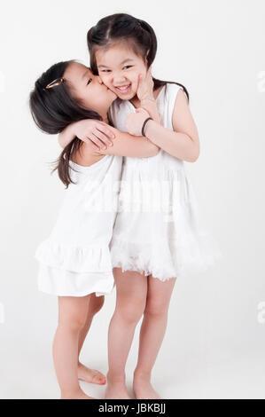 Las niñas retrato. Hermanas asiáticas besar sobre fondo liso. Hermano amor.