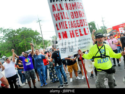 """Orlando, Florida, EE.UU. 12 Jun, 2017. Un hombre sostiene un cartel que dice """"Todos los homos se quemará como unos maricones en el infierno"""" en la fuente de los miembros de la comunidad LGBI durante un monumento a las 49 víctimas del tiroteo en la discoteca gay de pulso hace un año, en Orlando, Florida, Estados Unidos, 12 de junio de 2017. La ciudad de Orlando, rindió tributo a las 49 personas que fueron asesinadas en el club con mensajes de unidad y contra el odio. Crédito: Agencia de Noticias EFE/Alamy Live News"""