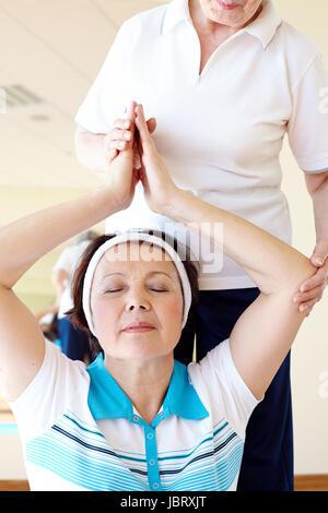Retrato de más viejas mujeres haciendo ejercicio de yoga con su instructor en el gimnasio de deportes