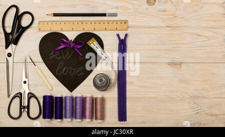 Accesorios de costura de color púrpura y el corazón con una inscripción - coser en el amor. El enfoque selectivo.