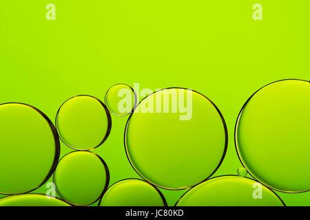 Gotas de aceite en el agua, las burbujas en el fondo abstracto verde Foto de stock