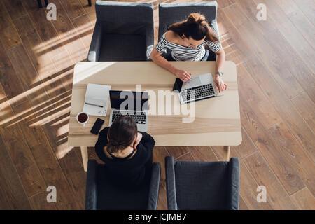 Inicio negocios y nueva tecnología móvil concepto con pareja joven en el moderno y luminoso interior oficina trabajando en el portátil y Tablet PC en el nuevo proyecto creativo e intercambiar ideas, antena vista desde arriba.