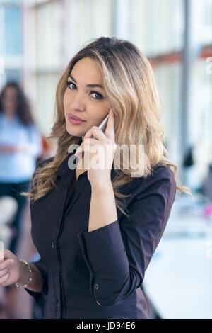 Retrato de joven empresaria en oficina sostiene su móvil